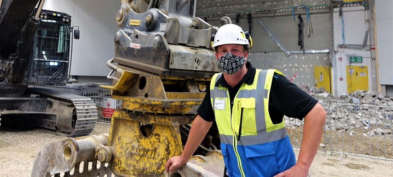 Oliver Reisenhofer mit Maske und Helm neben einem Bagger auf der Baustelle
