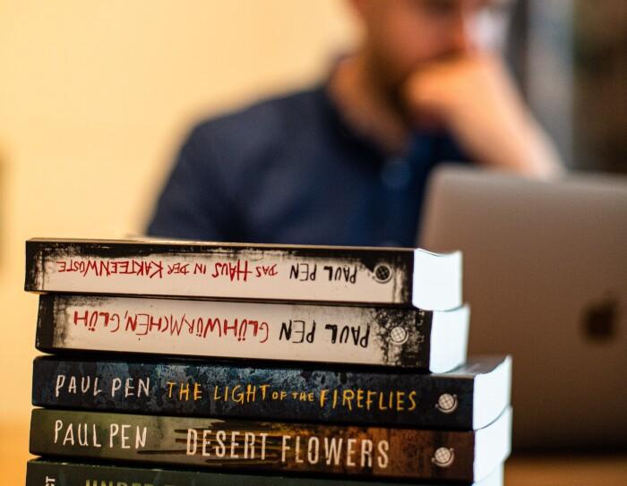Paul Pen Paul empezó su relación con Amazon Crossing, la editorial especializada en traducciones, en 2015. Tres de sus cuatro novelas se han publicado al inglés y al alemán. En primer plano aparecen sus tres novelas traducidas al inglés y otra en alemán. De fondo y desenfocado, Paul trabajando en su ordenador.