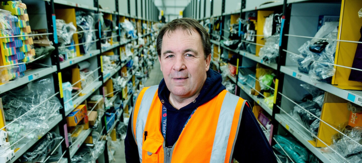 Paul Jones pictured in an orange high visibility vest with a long row of warehouse shelves in the background