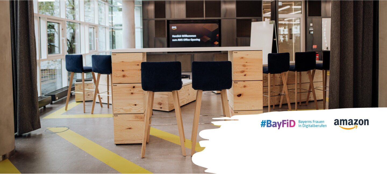 Zwei Holzhocker mit dunkel blauen Bezügen stehen an einem hohen Holztisch. Rechts sind die Logos von BayFID und Amazon zu sehen.