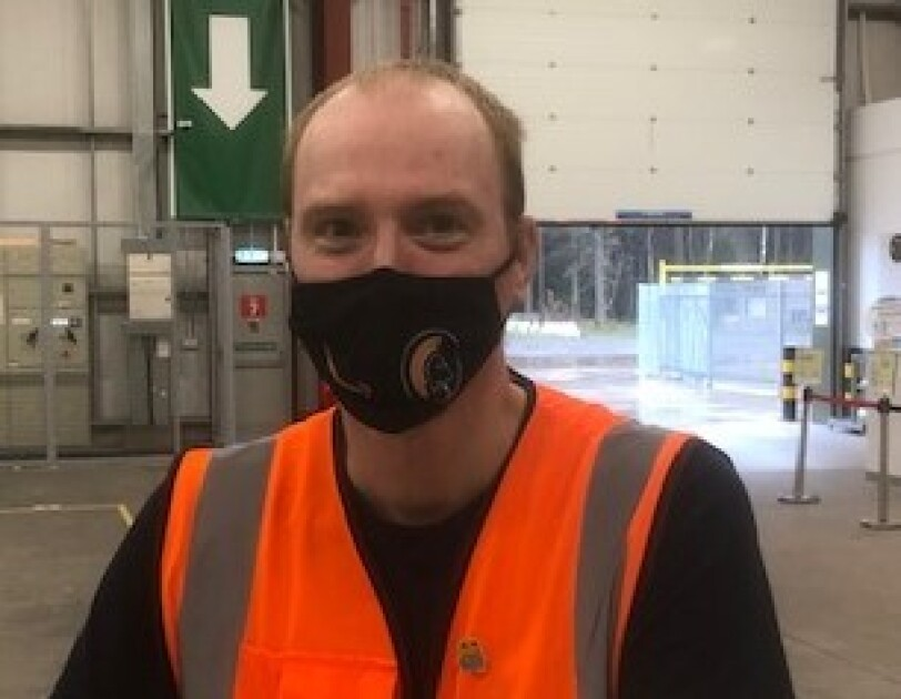 Alex Van Krimpen, temporary operations supervisor at Amazon's delivery station in Penrith pictured on the shop floor wearing a high visibility vest and a black face mask.