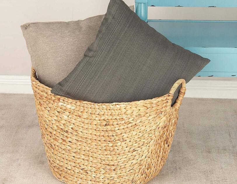 Two cushions in a woven grass basket, in front of an aqua bench.