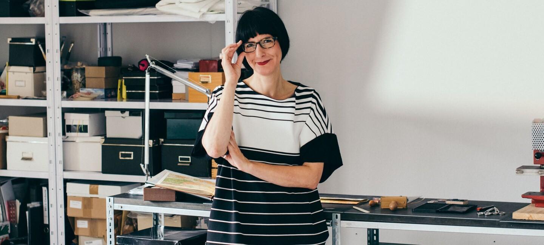 Christiane Hübner von renna deluxe in ihrer Werkstatt. Im Hintergrund sieht man Regale mit Kisten.