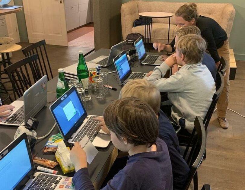 digital.engagiert_oderdojo_Kinder sitzen an einem langen Tisch, vor ihnen stehen Laptops. Eine Frau erklärt ihnen etwas.