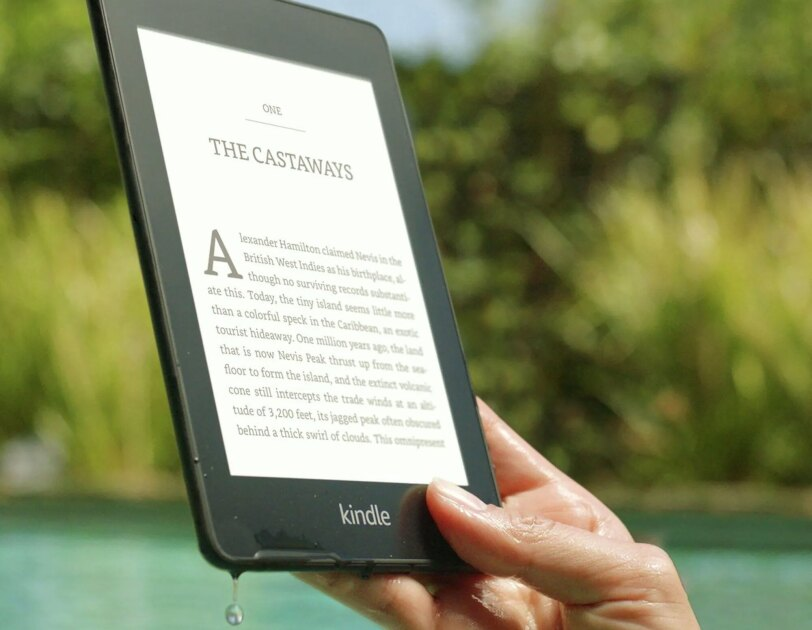 Waterproof Kindle Paperwhite being lifted out of a pool
