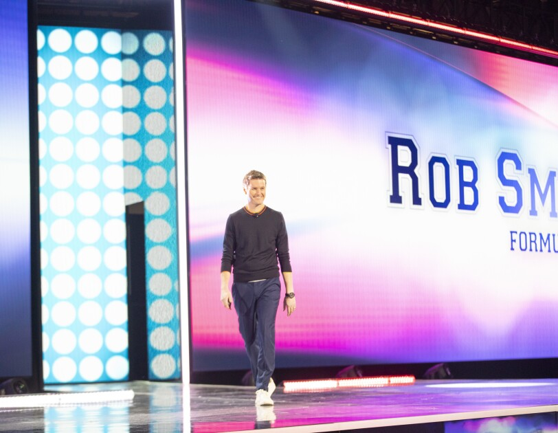 Rob Smedley, Formula 1 engineer standing on stage at the AWS re:Invent 2019 event. He is in front of a large screen with his name on it.