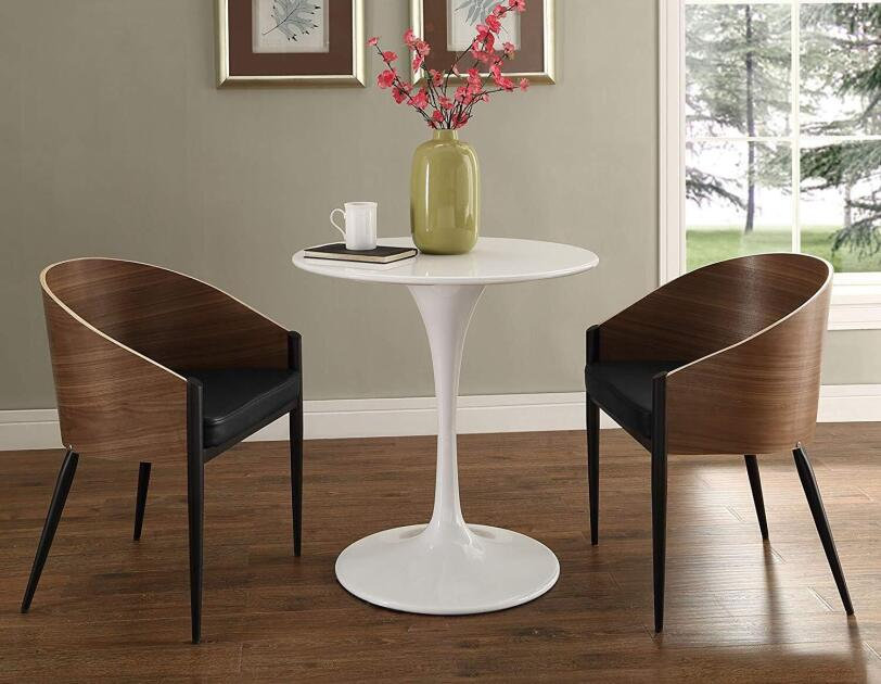 Two Philippe Starck-style wood chairs with pin legs sit on either side of a white lacquer pedestal table.