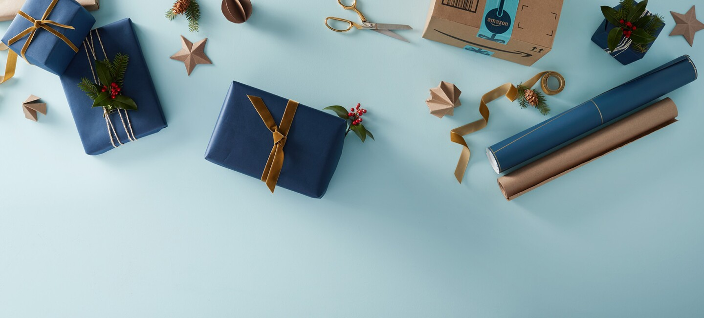 Four gift boxes are wrapped in navy blue paper, one with a thin brown ribbon, two with  metallic ribbon with evergreen bough and berries, and one with a thick brown ribbon. An Amazon box awaits wrapping, alongside navy and brown kraft papers, a scissor, and assorted decorations including ribbons, a pinecone and paper stars.