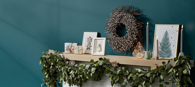 Weihnachtsgeschenke und Weihnachtsdeko stehen auf dem Kaminsims.