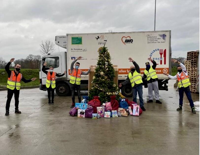 Gruppenbild mit Mitarbeiter von Amazon und der Tafel vor einem Tafel-Lkw. In der Bildmitte ein Weihnachtsbaum, unter dem Geschenke liegen.