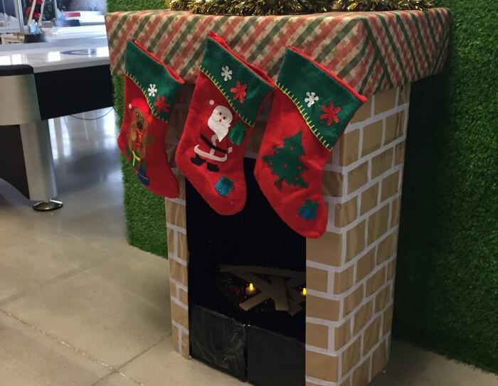 Adorno navideño de DQA4.  Chimenea hecha de cartçon con fuego simulados y los ters reyes magos encima. Del árbol cuelan tres calcetines de color rojo.