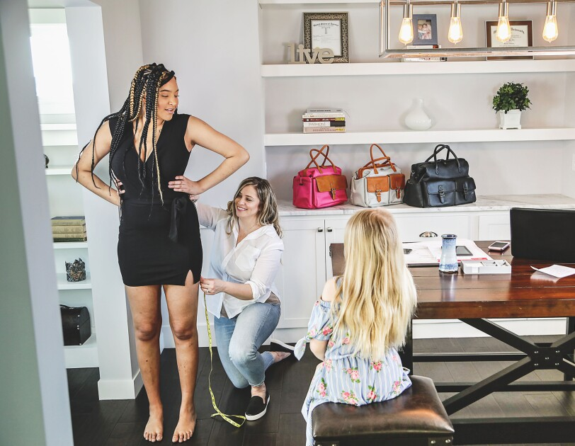 A woman kneels on the floor of her home office, holding up a measuring tape against the dress hem of the woman standing in front of her. A young girl is perched on a stool near a large desk, watching the process.