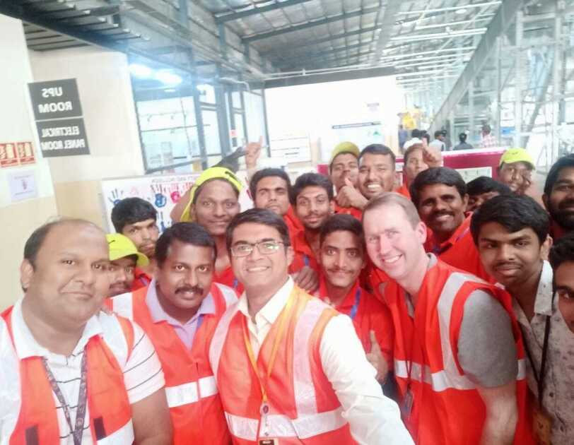 Deaf Associates in red vests take a selfie with John Felton on his visit to India