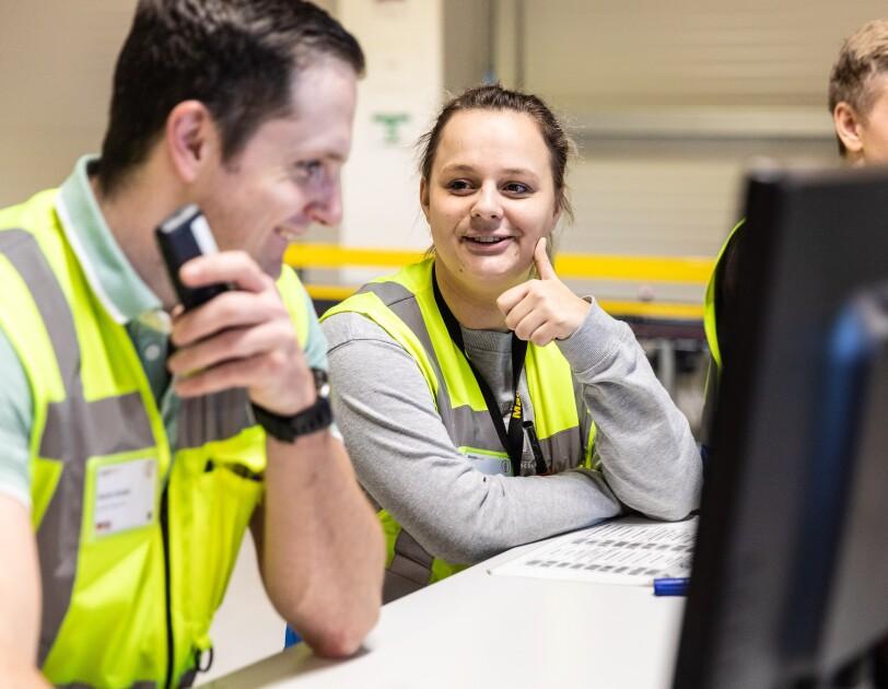 Amazon Logistik Mitarbeiter im FC, sie tragen gelbe Sicherheitswesten, sie stehen am Schreibtisch vor Bildschirmene und unterhalten sich