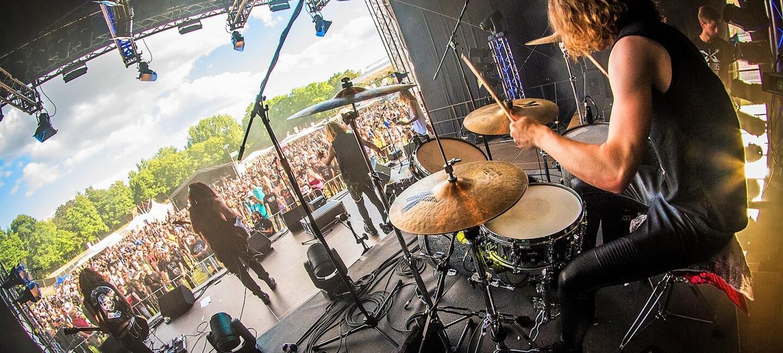 Blick von der Bühne: Man sieht einen Schlagzeuger, vor ihm weitere Bandmitglieder: Ihr Blick geht in die Menge, wo sich die Zuschauer vor der Bühne aufgebaut haben.