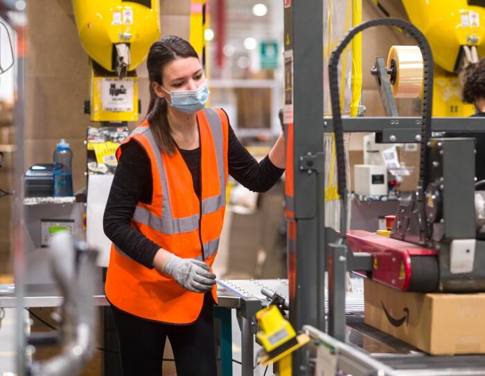 Inquadratura di una dipendente di un magazzino Amazon che sta maneggiando un attrezzo per apporre etichette sui pacchi. In basso a destra si intravede un pacco sotto la pressa che incolla le etichette.