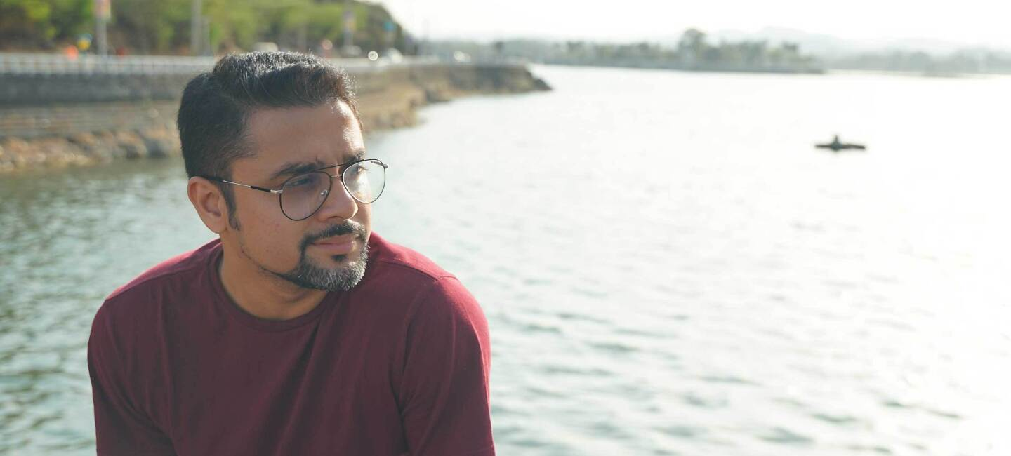 Author Novoneel Chakraborty sits by the water