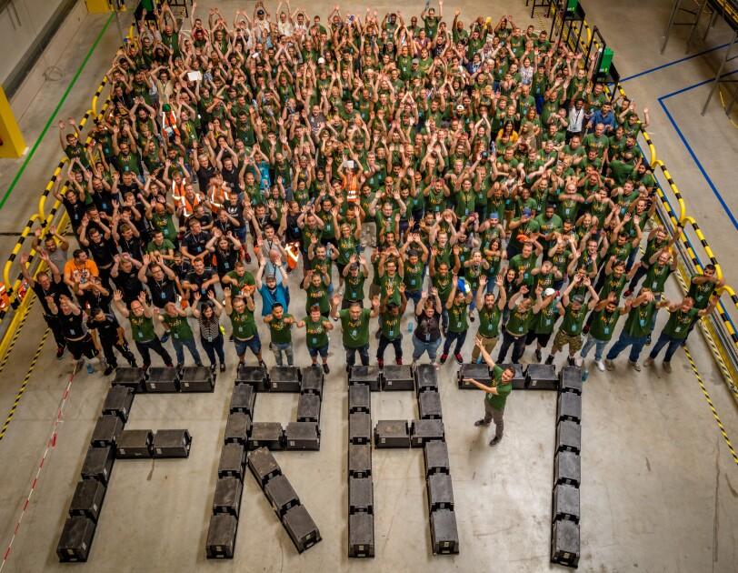 """Blick von oben auf die Lagerhalle, in der sich ca. 300 Mitarbeiter des Logistikszentrums eingefunden haben. Die Hände sind zur Laola ausgebreitet. Vor ihnen wurde das Logo """"FRA7"""" auf dem Boden der Halle mit schwarzen Transportkisten nachgebildet. Inmitten des Logos steht der Standortleiter und weist auf die Mitarbeiter."""