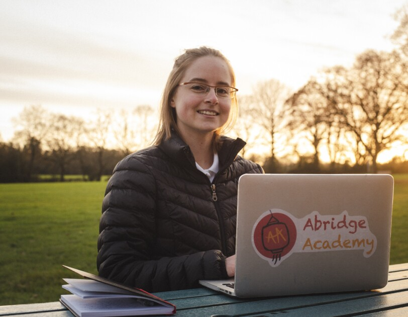Katie Prescott, founder of Abridge Academy, working on her laptop