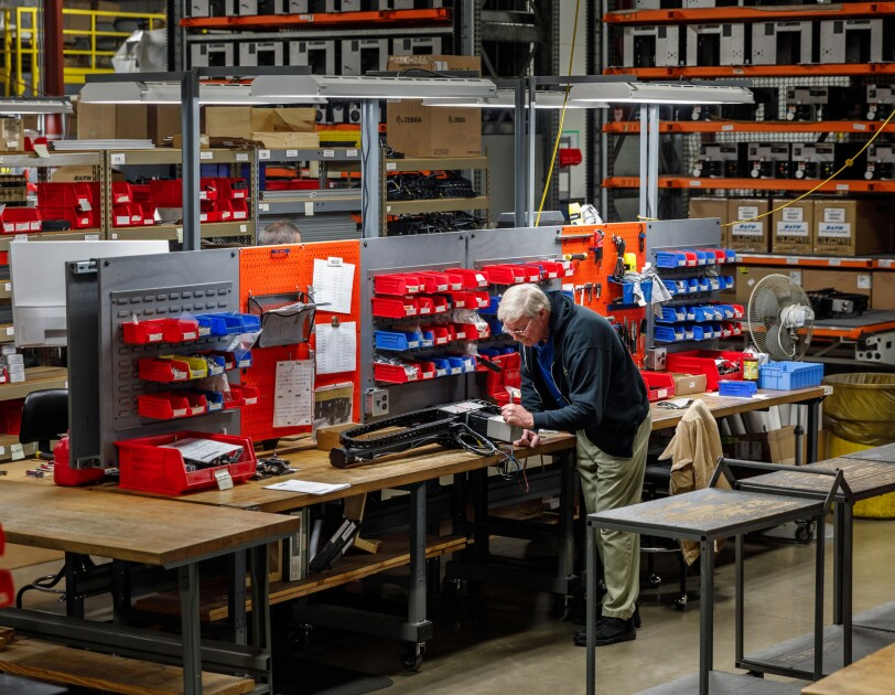 A man works in a manufacturing space with high shelves and workbenches.