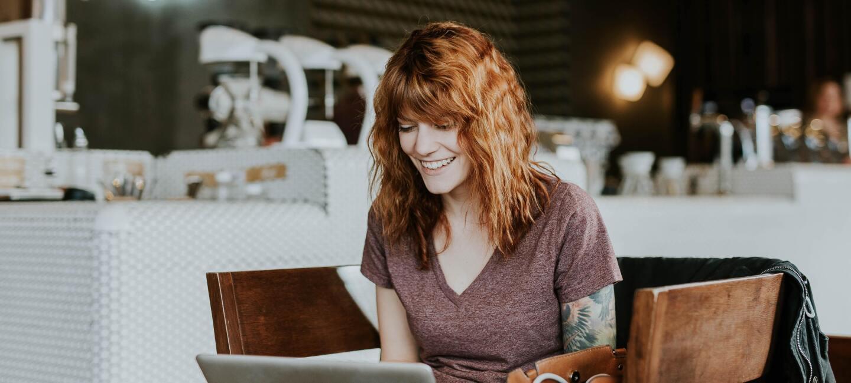 Eine Frau mit roten Locken sitzt vor einem Laptop und lächelt.