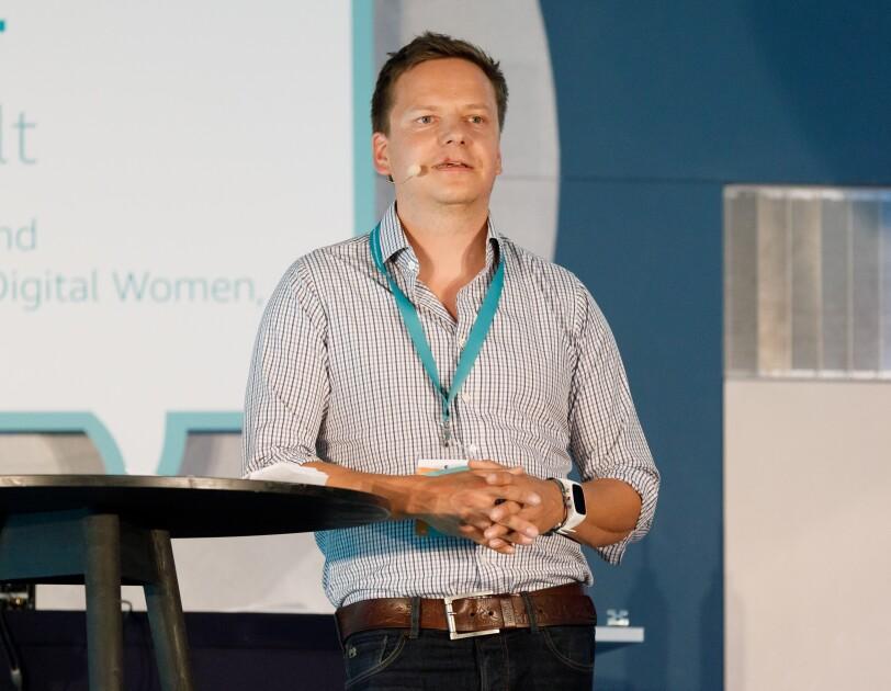 Markus Schöbel steht auf der Bühne und lehnt sich seitlich an das Rednerpult. Er blickt zum Publikum und spricht zu ihm.