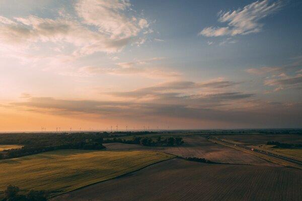 The Climate Pledge_Amazon_Felder im Sonnenuntergang_Windräder