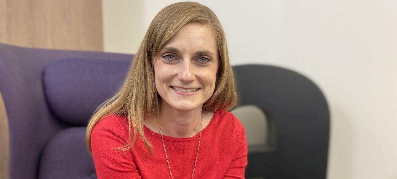 Marzjanna Wollnik sitzt auf einer Couch und schaut lächelnd in die Kamera