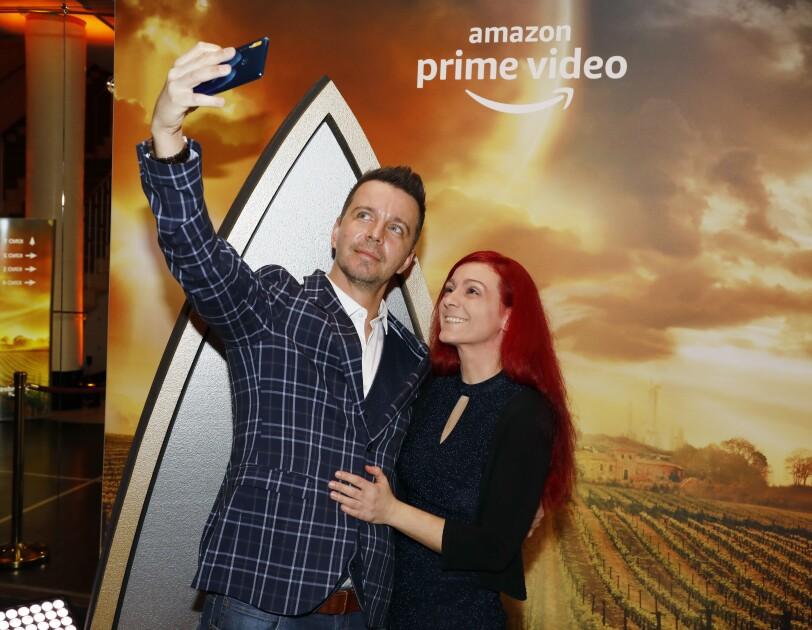 Ein Mann im karierten Sakko und eine rothaarige Frau machen ein Selfie. Im Hintergrund: das Star Trek Symbol und das Prime Video Logo.