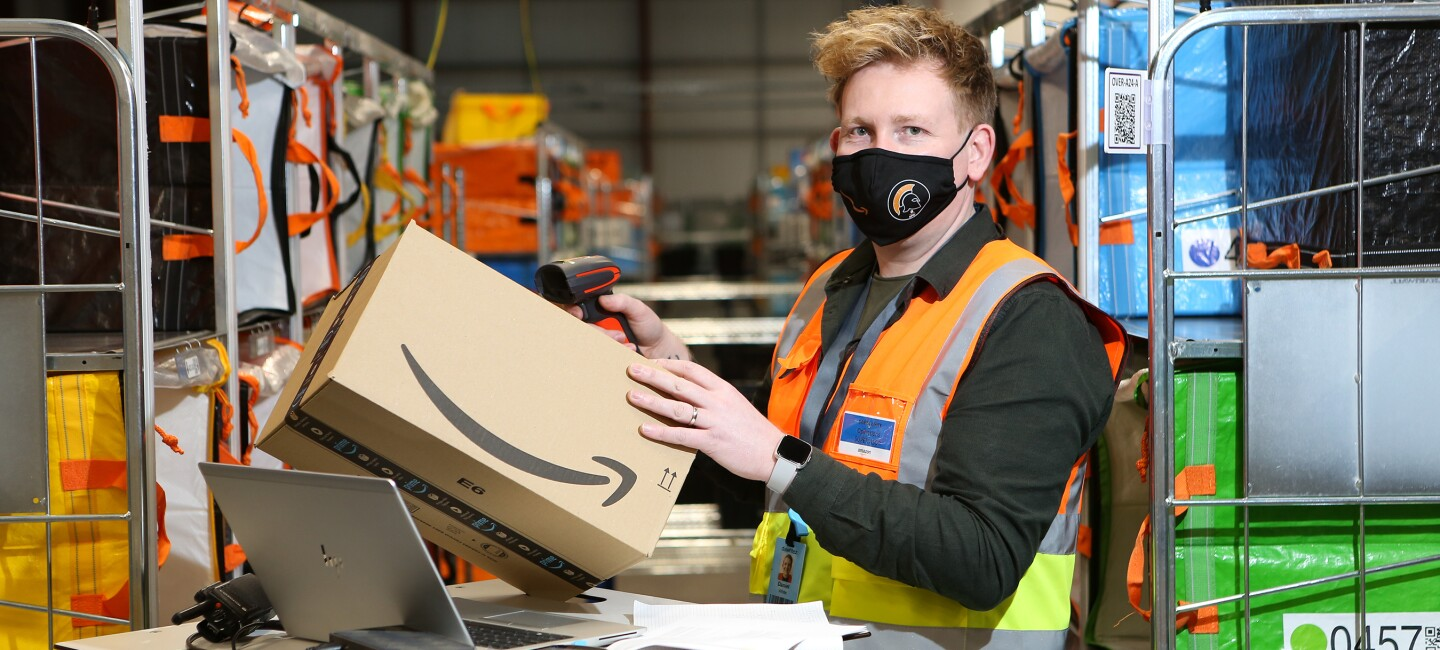 Dan White, Operations Supervisor at Amazon's delivery station in Penrith pictured wearing a high visibility vest and a face mask.