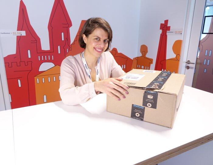 Ritratto di Marianna Pietrafesa, Responsabile europea del marketing per Amazon Locker e Pickup. La donna siede dietro un tavolo e poggia la mano destra su una scatola Amazon, poggiata di fronte a lei. Sullo sfondo un muro colorato nell'ufficio Amazon di Lussemburgo.
