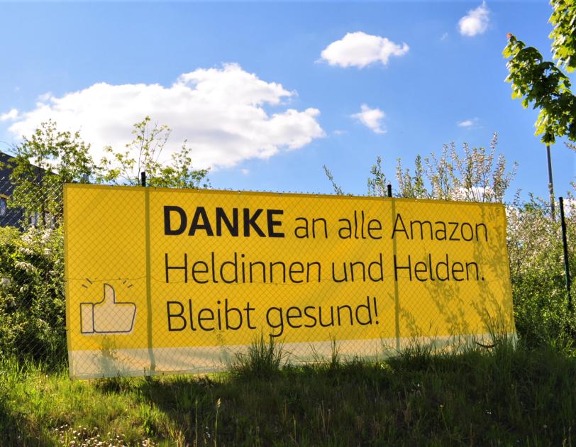 Gelbes Banner mit Aufschrift: Danke an alle Amazon Heldinnen und Helden. Bleibt gesund!
