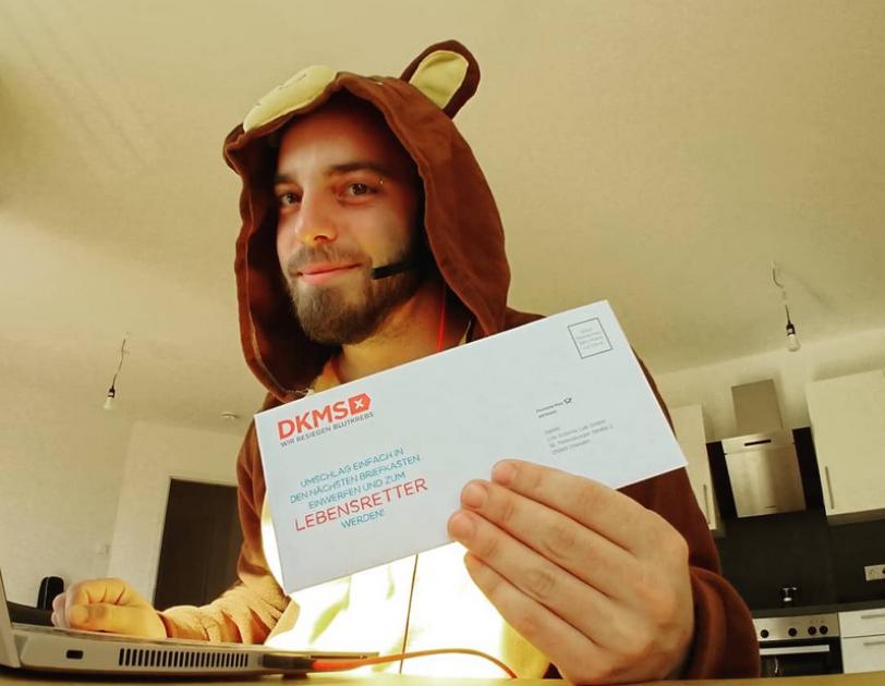 Ein Mann mit Teddybärenkostüm sitzt vor einem Laptop und hält einen Zettel der DKMS in die Kamera. Er lächelt.