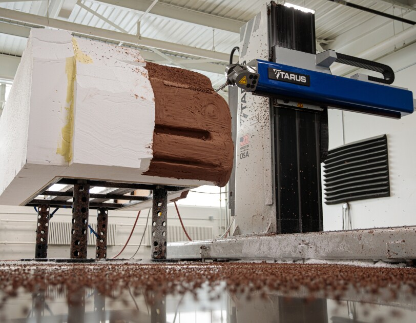 An large milling device carves a Styrofoam model.