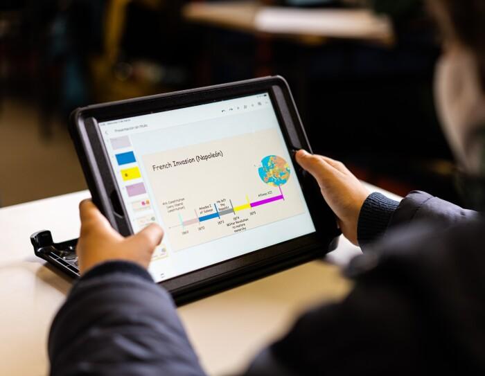Amazon Digital Lab es un mundo de recursos digitales gratuitos para usar en el aula y en casa. Un plano desenfocado de un alumno con una tableta en la mano y habla de historia, de la invasión de Napoleón, en inglés.  El chico agarra la tableta con las manos.