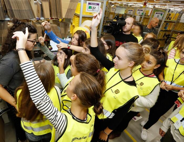 Las participantes de la jornada greenlight for girls realizaron un tour por un centro logístico de Amazon. En la foto, 15 participantes, algunas de ellas con el brazo en alto, se ofrecen voluntarias para empaquetar un pedido. Todas ellas lucen un chaleco amarillo, En la parte izquierda de la foto, la responsable del tour, y en la parte izquierda, al fondo, el cámara.