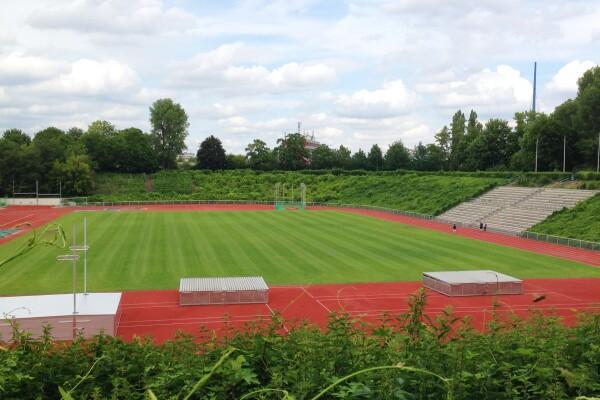 Ein Stadion mit roter Rennbahn und Rasenfläche in der Mitte ist auf dem Foto zu sehen.