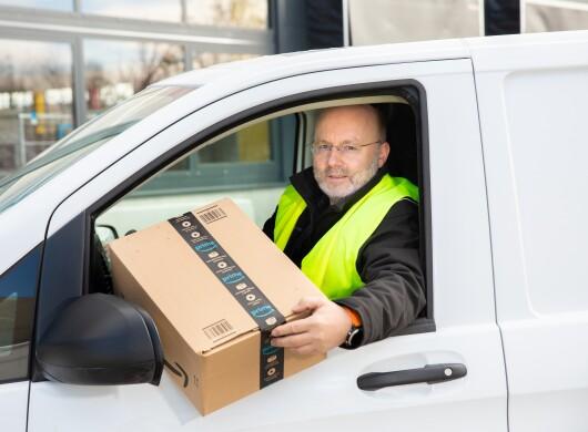 Ein Herr mit grauem Bart und Brille in einem Lieferfahrzeug.