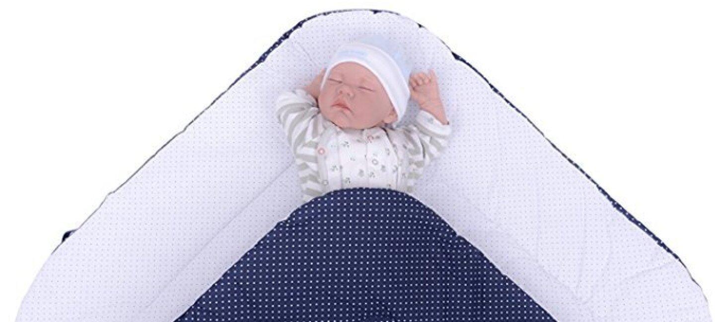 Un nourrisson dort, les bras levés, sur un matelas bleu à pois blancs. Il porte un pyjama blanc et gris et un bonnet blanc.