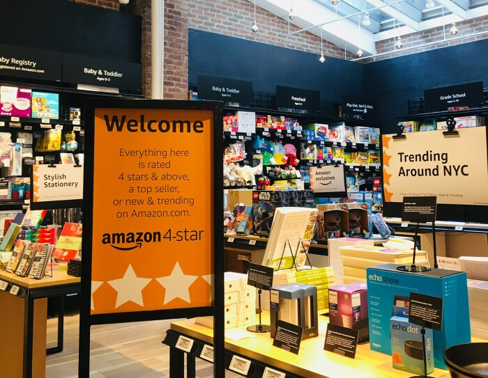 "View inside Amazon 4-star. In the foreground, a sign that says ""Welcome Everyting here is rated 4 stars & above, a top seller, or new & trending on Amazon.com. Next to the sign is a display table with products on it, and a ""Trending Around NYC"" sign. Some items on the table include Echo Show, Echo Dot, books and more. In the background, baby registry, baby and toddler products, grade school items, and more."