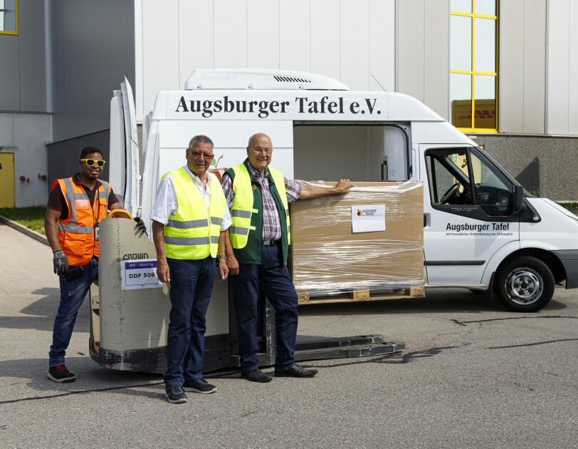_Ein Logistikmitarbeiter mit gelber Sonnenbrille fährt via Scherenhubwagen die Paletten zum Lieferwagen der Augsburger Tafel. Mit im Bild: die beiden Vertreter der Augsburger Tafel.