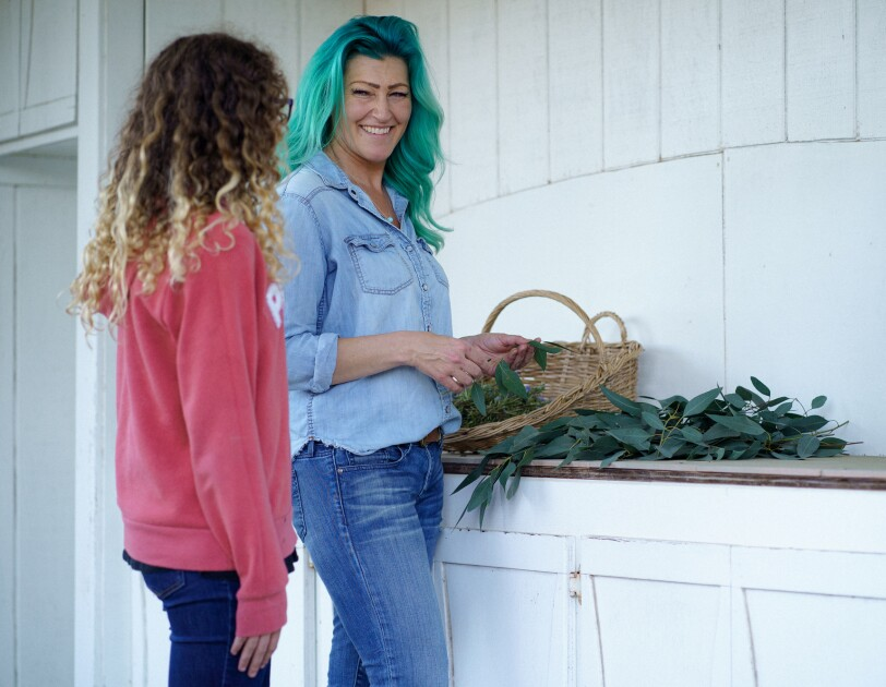 A woman and a girl stand next to a counter that's covered in plants.