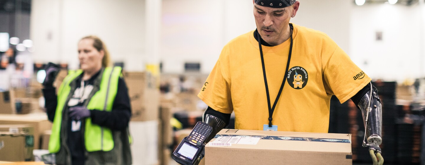 A man with dual arm prosthetics goes to lift a box in a large warehouse space. He wears a yellow Amazon branded t-shirt.