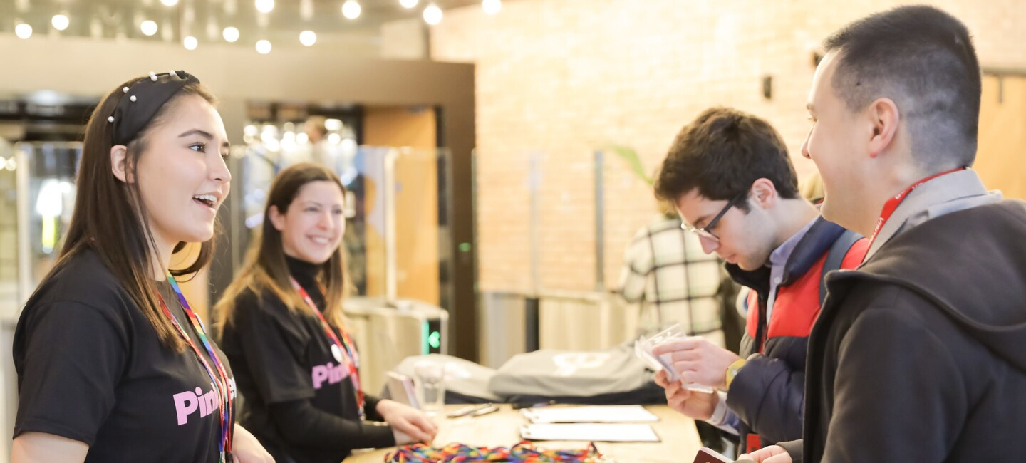 Visitors receiving entry passes for the LGBT Leaders in Stem event at the reception area of Amazon's London head office.