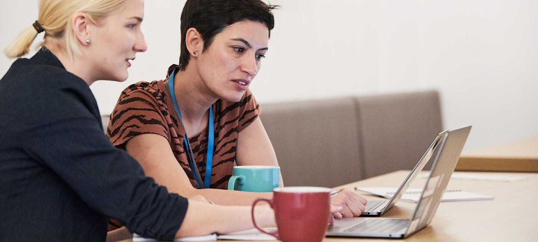Zwei Frauen sitzen an einem Holztisch und schauen in einen Laptop. Auf dem Tisch stehen zwei Kaffeetassen.