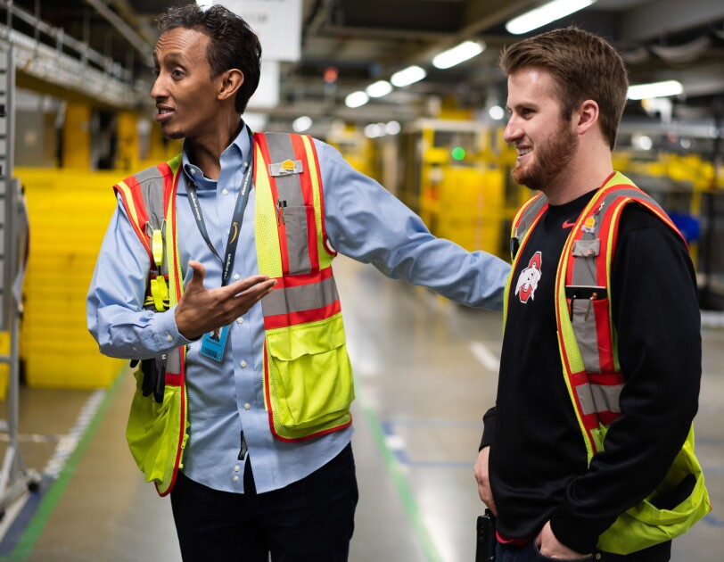 Two men stand together. Both wear brightly colored safety vests. The man on the light gestures toward the man on the left.