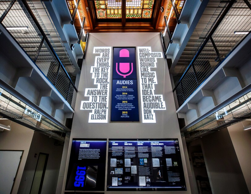 An atrium space decorated with a large graphic of a microphone.