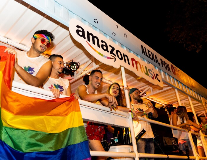 Carroza de glamazon durante el desfile del Día internacional del orgullo LGTBI en Madrid. Ya es de noche y dos chicos con las camisetas de glamazon cuelgan la bandera del arcoiris en la carroza. La carroza está llena de gente que observa a los asistentes al desfile que se encuentran en la calle. En la carroza está el logo de Amazon Music y el lema Alexa, pon orgullo.