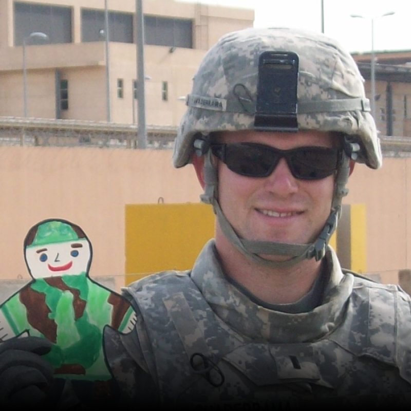 Aaron Guaderrama smiles as he holds up a paper cut-out drawing of a military member. He is wearing his military uniform and helmet.