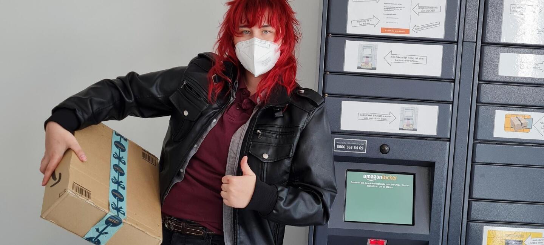 eine Frau mit roten Haaren, Lederjacke und Maske vor einem Amazon Locker: Sie hat ein Amazon Päckchen in der Hand.